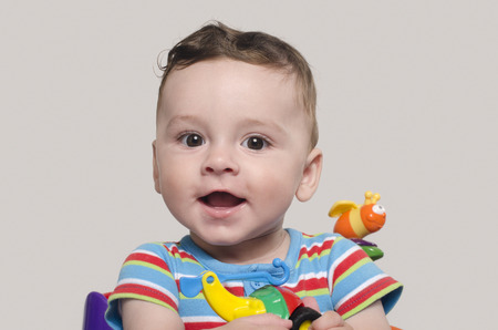 six month old: Cute baby boy sitting and playing with toys. Adorable six month old child happy laughing. Stock Photo