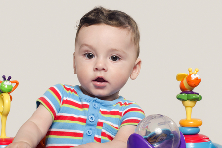 six month old: Cute baby boy sitting and playing with toys. Adorable six month old child happy looking surprised raising his eyebrow.