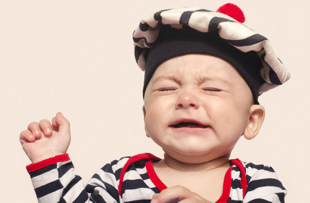 teething: Cute baby boy crying raising his hands up. Little child in pain, suffering, teething, refusing and crying. Cute sad baby dressed nautical.