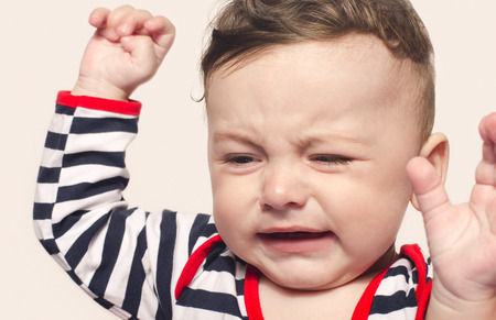 refusing: Cute baby boy crying raising his hands up.  Little child in pain, suffering, teething, refusing and crying. Cute sad baby throwing a tantrum.
