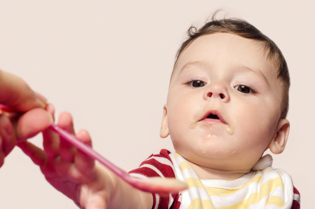 six month old: Mother hand feeding infant baby food. Child trying to grab the spoon.  Six month old beginning food diversification. Cute baby boy eating food with the spoon.