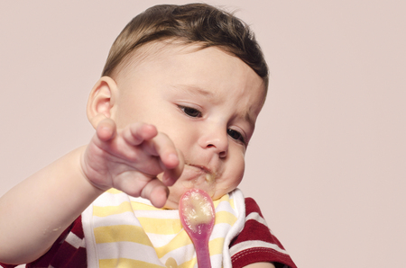 refusing: Cute baby refusing to eat baby food from the spoon. Six month old beginning food diversification. Little child cringing and pushing the spoon with food. Stock Photo
