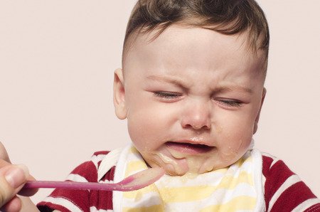 six month old: Mother hand feeding food to baby crying. Six month old beginning food diversification.Cute baby boy refusing to eat food with the spoon.
