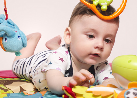 playmat: Cute baby boy sitting on a playmat and playing with toys. Adorable six month old child happy crawling to reach the toys.