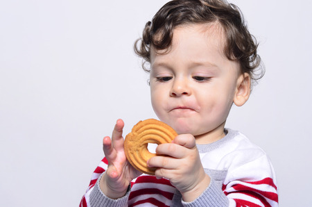curiously: Portrait of a cute baby eating a biscuit looking at it curiously. One year old kid eating biscuits by himself. Adorable curly hair boy being hungry.