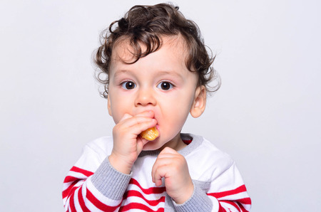 Portrait of a cute baby eating orange. One year old kid eating fruits by himself. Adorable curly hair boy being hungry biting on a slice of orange.