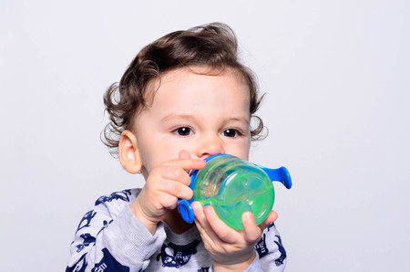 Portrait of a cute toddler drinking water from the bottle. One year old kid holding up the baby cup. Adorable curly hair boy being thirsty.