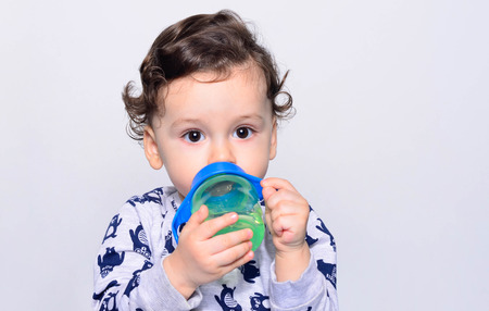 Portrait of a cute toddler drinking water from the bottle. One year old kid holding the baby cup. Adorable curly hair boy being thirsty. Reklamní fotografie
