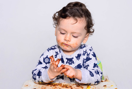mess: One year old kid eating a slice of birthday smash cake by himself getting dirty. Portrait of a cute baby eating cake making a mess. Adorable curly hair boy being hungry. Kid eating sweets.