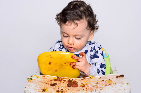 One year old kid eating a slice of birthday smash cake by himself getting dirty. Portrait of a cute baby eating cake making a mess. Adorable curly hair boy being hungry. Kid eating sweets.
