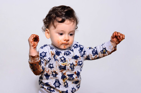 One year old kid after eating a slice of birthday smash cake by himself getting dirty. Portrait of a cute baby running after making a mess. Adorable curly hair boy being very dirty.