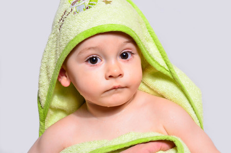 Portrait of an adorable baby boy wearing a towel after bath. One year old kid looking up clean after bath routine. Cute toddler wet wrapped in a green towel. Reklamní fotografie