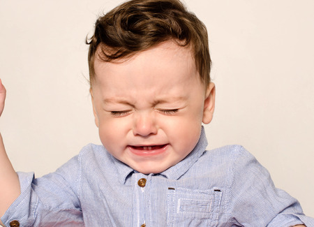 Cute baby boy crying. Little child in pain, suffering, teething, refusing and crying. Cute sad baby throwing a tantrum.Baby wants up in the arms to be held.