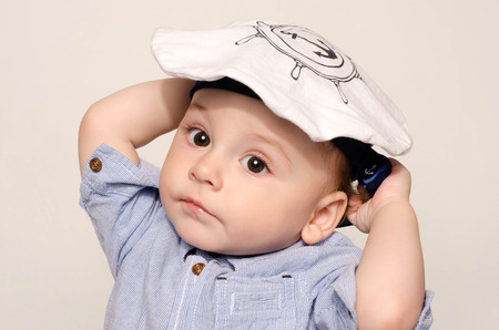 Portrait of a cute baby boy looking at camera wearing a sailor hat. Adorable child with a nautical hat. Reklamní fotografie