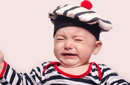 Cute baby boy crying. Little child in pain, suffering, teething, refusing and crying. Cute sad baby dressed nautical. Reklamní fotografie