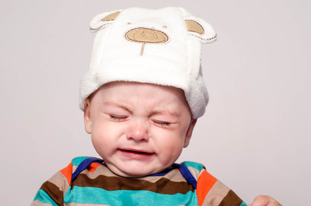Cute baby boy with adorable hat crying. Little child in pain, suffering, teething, refusing and crying. Cute sad baby throwing a tantrum. Baby wants up in the arms to be held. Reklamní fotografie