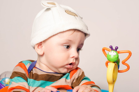 Baby boy with a cute hat sitting and playing with toys. Adorable six month old child looking curious at a butterfly toy. Reklamní fotografie