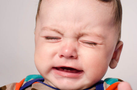 Cute baby boy crying. Little child in pain, suffering, teething, refusing and crying. Cute sad baby throwing a tantrum. Baby wants up in the arms to be held.