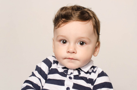 Portrait of a cute baby boy looking at camera with his big eyes.  Adorable child wearing a striped blouse with bow tie.