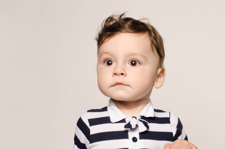 Portrait of a cute baby boy looking away surprised with his big eyes. Adorable child wearing a striped blouse with bow tie looking to the side.