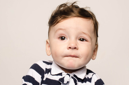 Portrait of a cute baby boy looking up cringing making a funny face lifting his eyebrow wondering. Adorable naked child making cute mimic. Reklamní fotografie