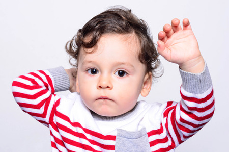 Portrait of a cute curly hair baby boy lifting his hands up. Adorable one year old child wanting to be held up.