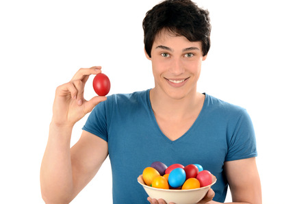 Handsome man holding up a red Easter egg and a basket with colorful dyed eggs.Young man smiling with a red egg in the hands. Isolated on white background. Happy Easter!