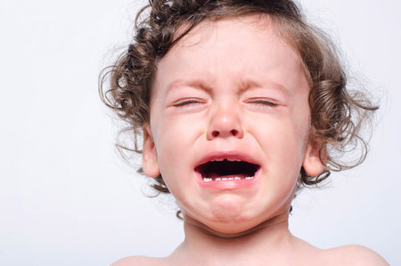 Portrait of a baby boy upset crying. Close up on cute toddler sad and sick teething screaming in pain.