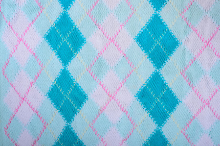 Close up on knit woolen fabric texture. Blue rhombus woven sweater as a background.