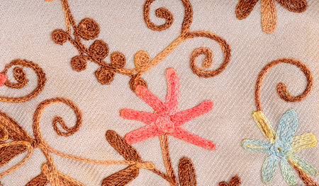 Close up on embroidered fabric with flowers. Brown fabric with flowers sewn as a background.