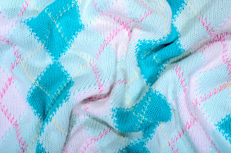 Close up on crumpled knit woolen  fabric  texture. Blue rhombus woven sweater as a background.
