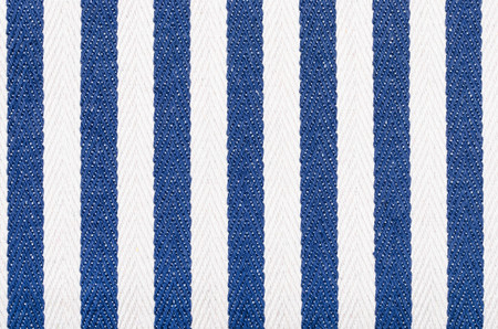 Close up on striped woven  fabric texture. Blue navy and white vertical stripes as a background. Reklamní fotografie