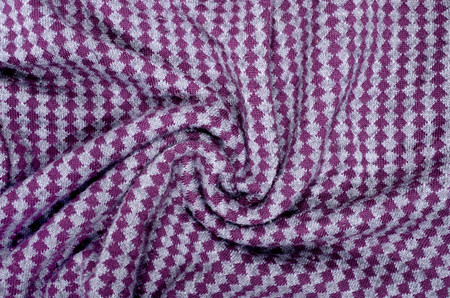 Close up on crumpled knit woolen  fabric texture. Grey and purple rhombus woven sweater as a background. Reklamní fotografie