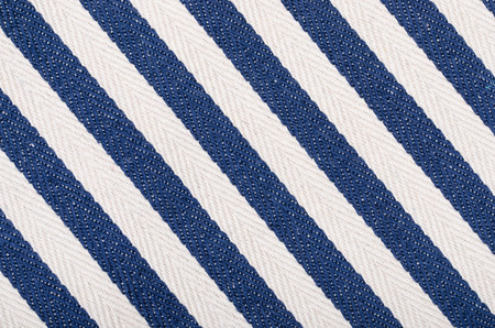 Close up on striped woven fabric  texture. Blue navy and white diagonal stripes as a background.