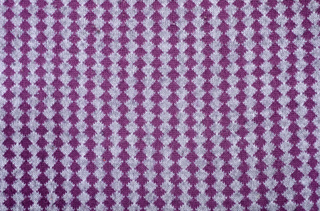 Close up on vertical knit woolen  fabric texture. Grey and purple rhombus woven sweater as a background. Reklamní fotografie