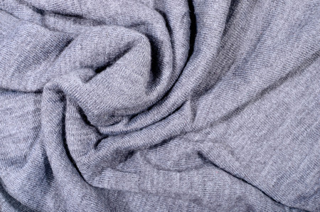 Close up on crumpled knit woolen  fabric texture. Grey woven sweater as a background.