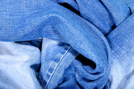 Close up on crumpled denim  fabric texture. Blue jeans close up on pants as a background.