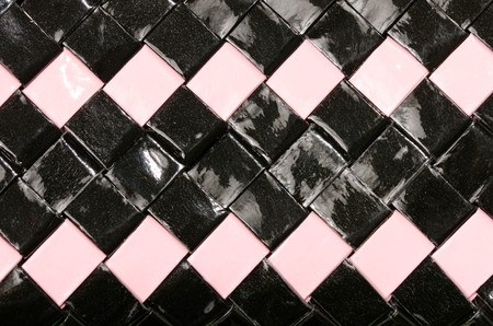 Close up on shiny plastic texture. Black and pink woven squared surface as a background. Reklamní fotografie