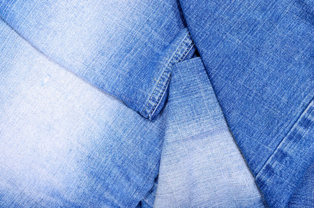 Close up on folded denim  fabric texture. Blue jeans close up on pants as a background.