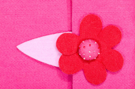 Close up on pink felt flower on fabric. Fucsia fabric with a red flower with beads as a background. Reklamní fotografie