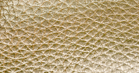 Close up on shiny gold faux leather texture. Old scratched surface as a background.