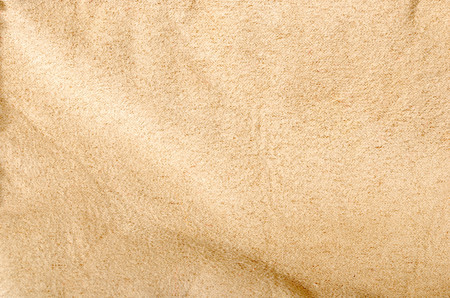 Close up on crumpled light brown fabric. Beige textile surface as a background. Reklamní fotografie