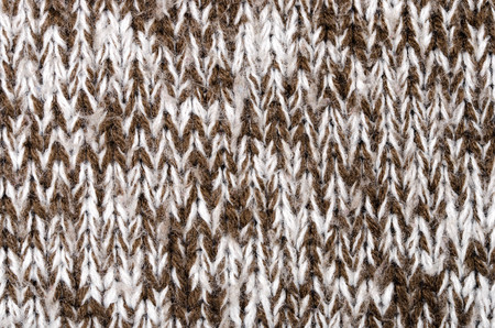 Close up on knit woolen fabric texture. Brown and white woven sweater as a background.