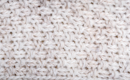 Close up on knit woolen fabric texture. White woven sweater as a background.
