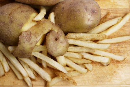 Peeled potato and french fries on wood concept photo