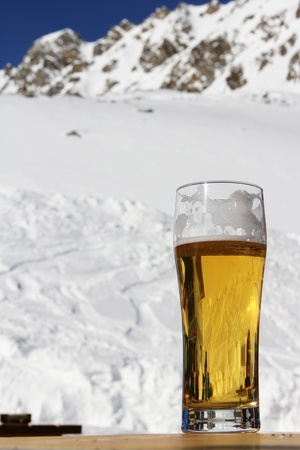 Glass of beer standing on table in high mountain cafe photo
