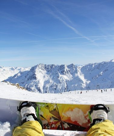 Snowboarder sitting on snow in high mountains photo