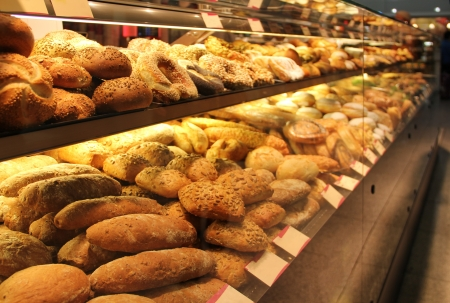 different appetizing bread on showcase in supermarket photo