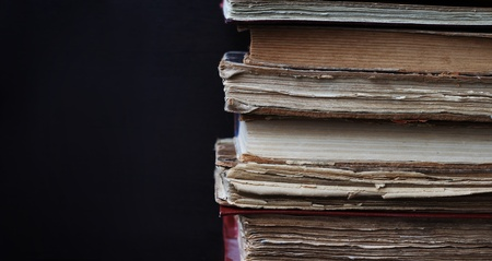 Stack of old books on dark background photo