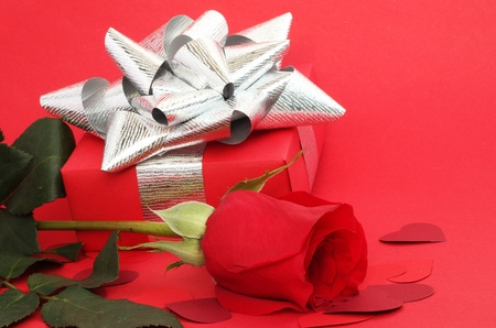Valentines Day gift in box with rose and small hearts on red background photo